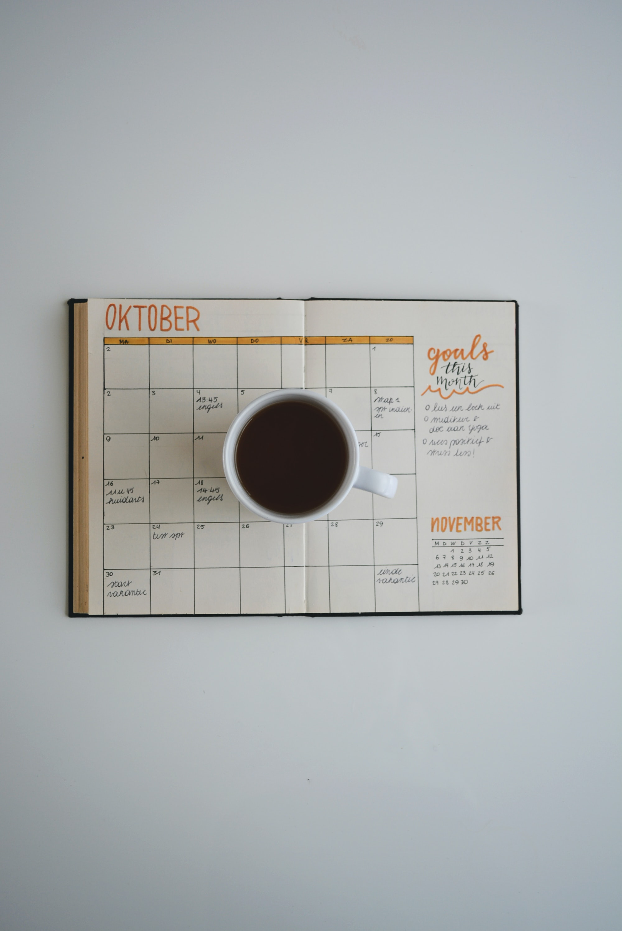 white coffee mug on calendar at october
