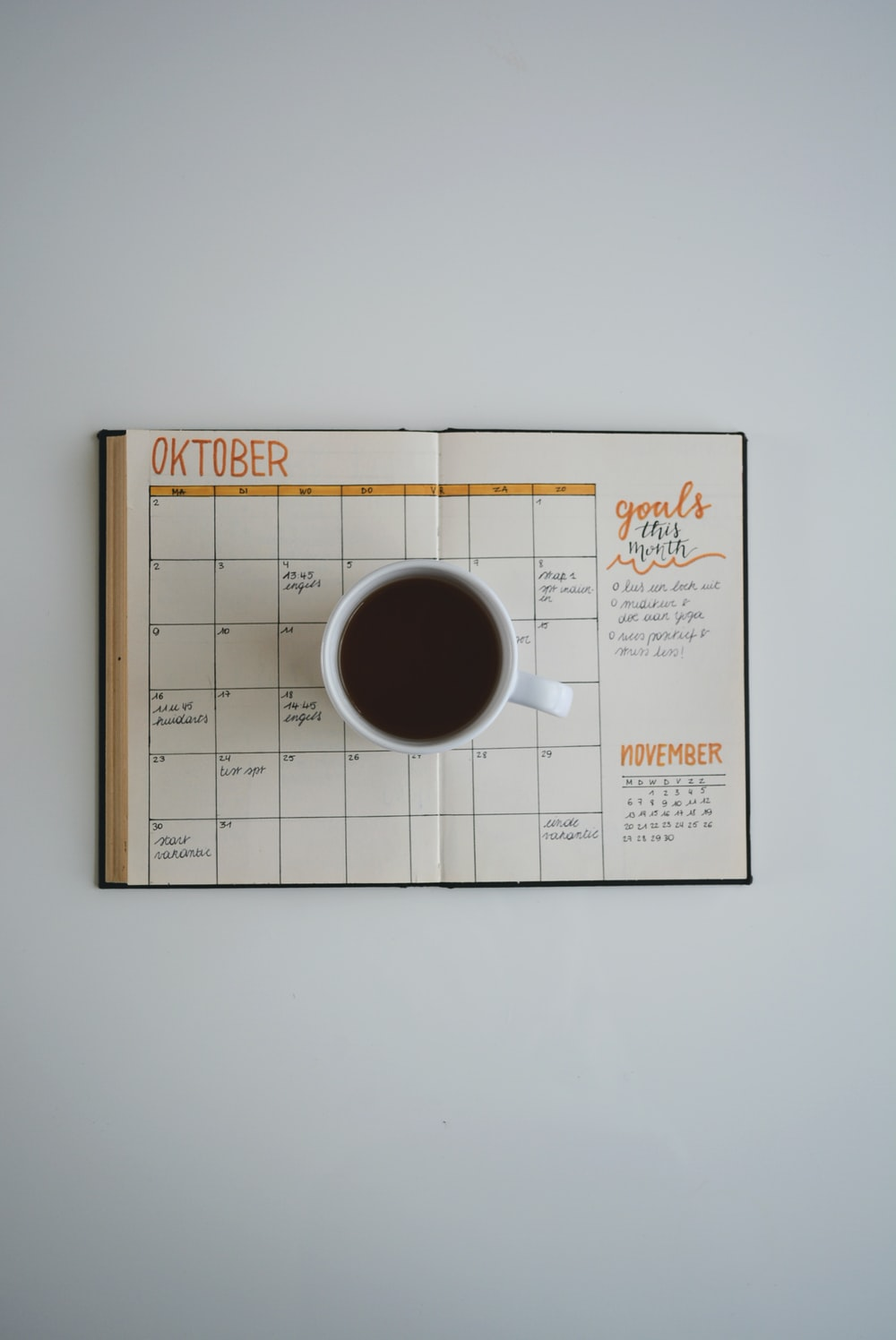 white coffee mug on calendar at october