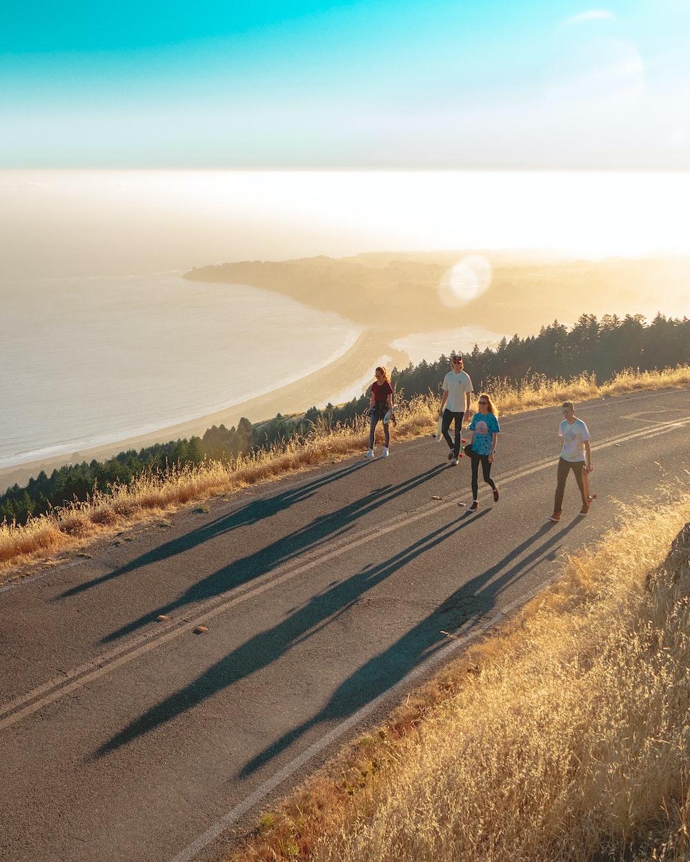four men and women walking on roadway near body of water