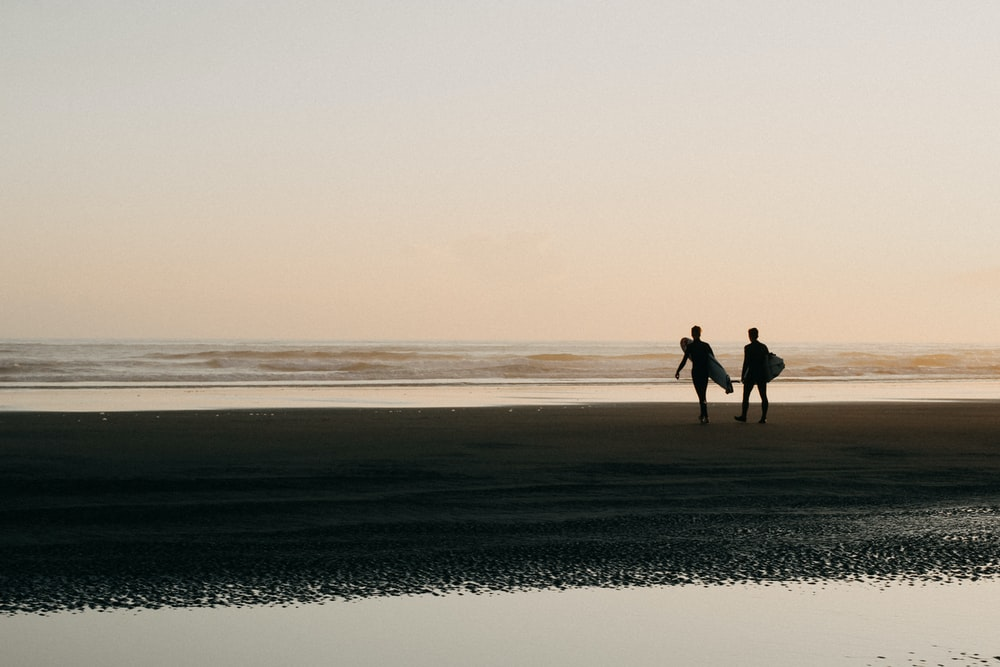 two persons holding surfboards on shoreline