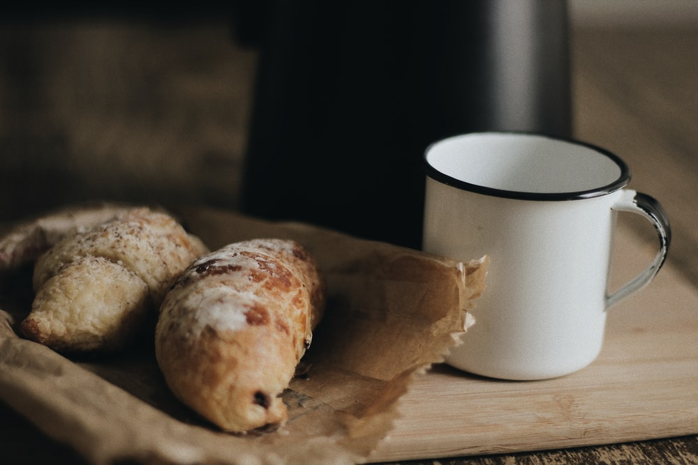 two breads on paper bag beside cup