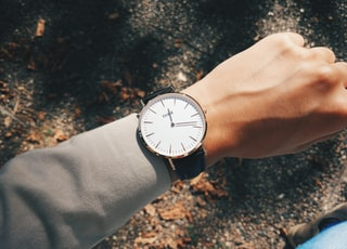 person wearing round silver-colored analog watch at 1:19