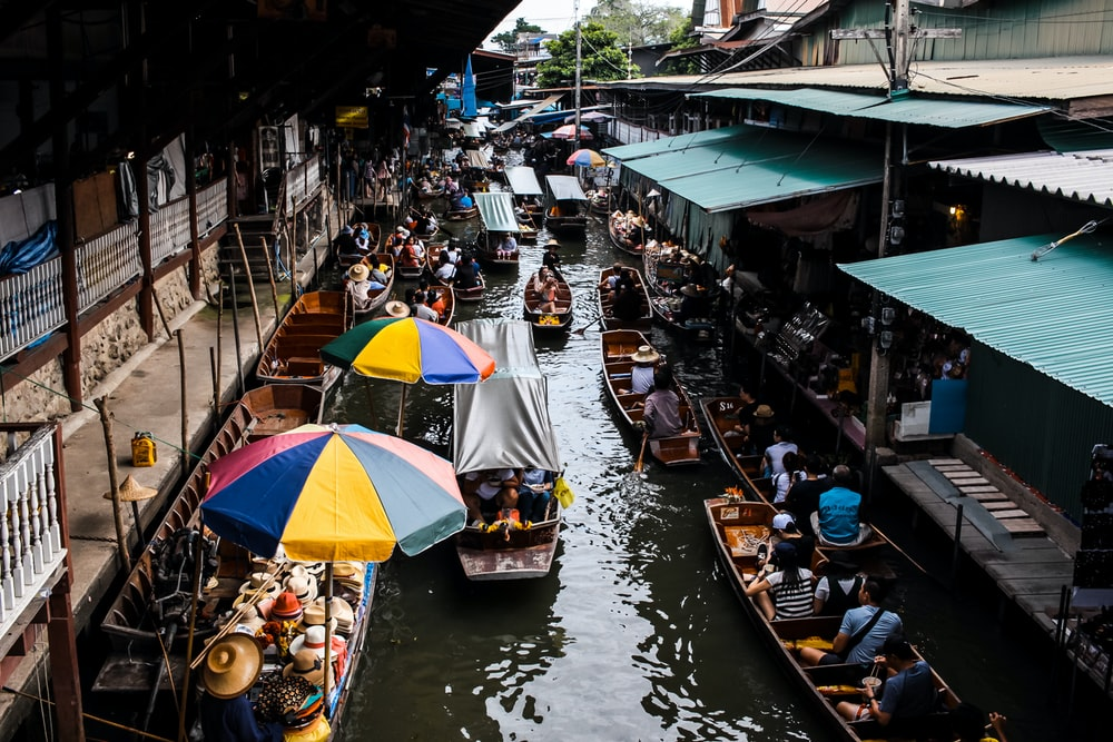 people riding boat in river near marketplace during daytime