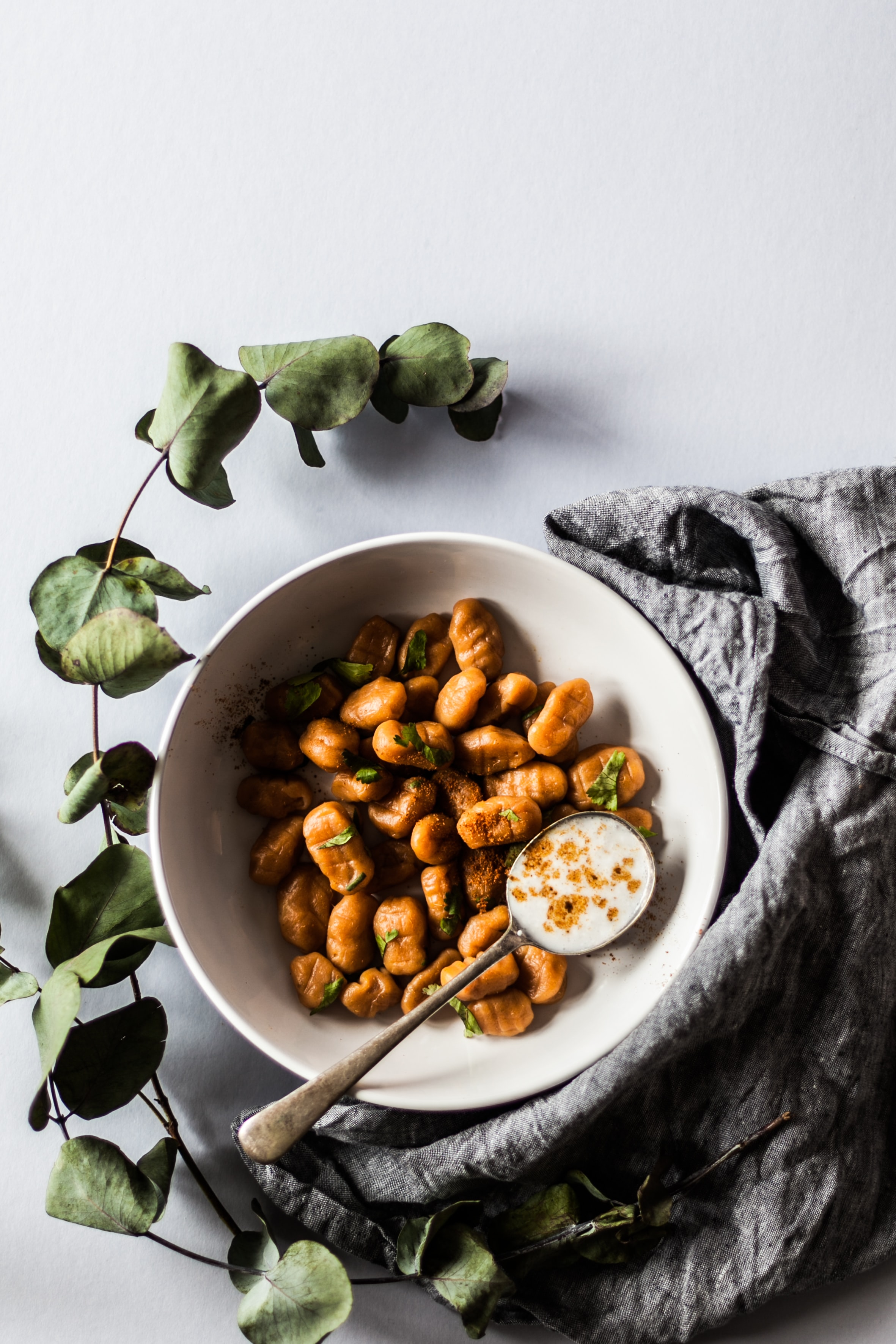 bowl of nuts with spoon beside green leaves