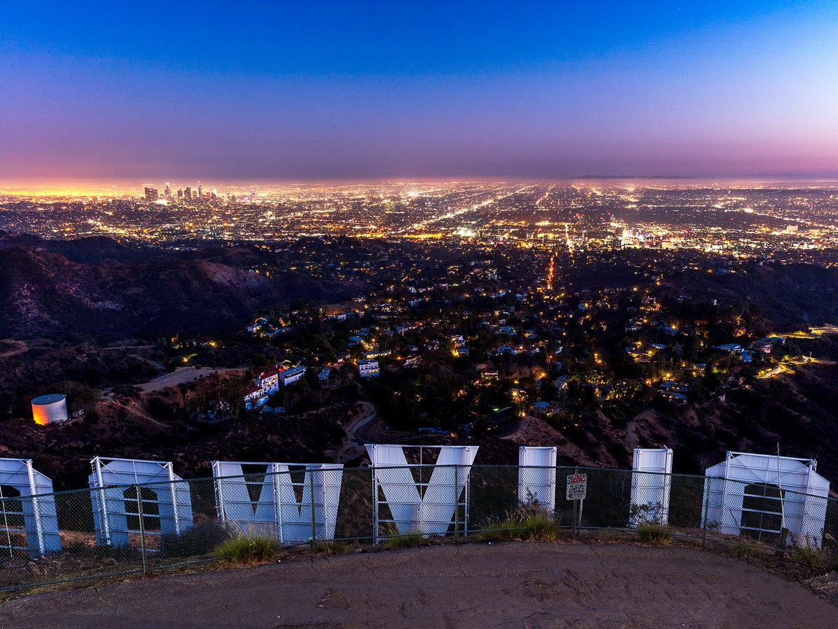 Above the Hollywood sign, lights of the city twinkling below.