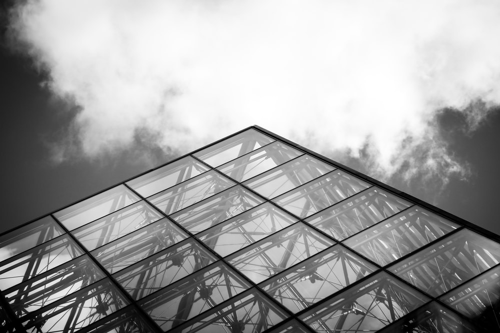 grayscale photography of curtain wall building