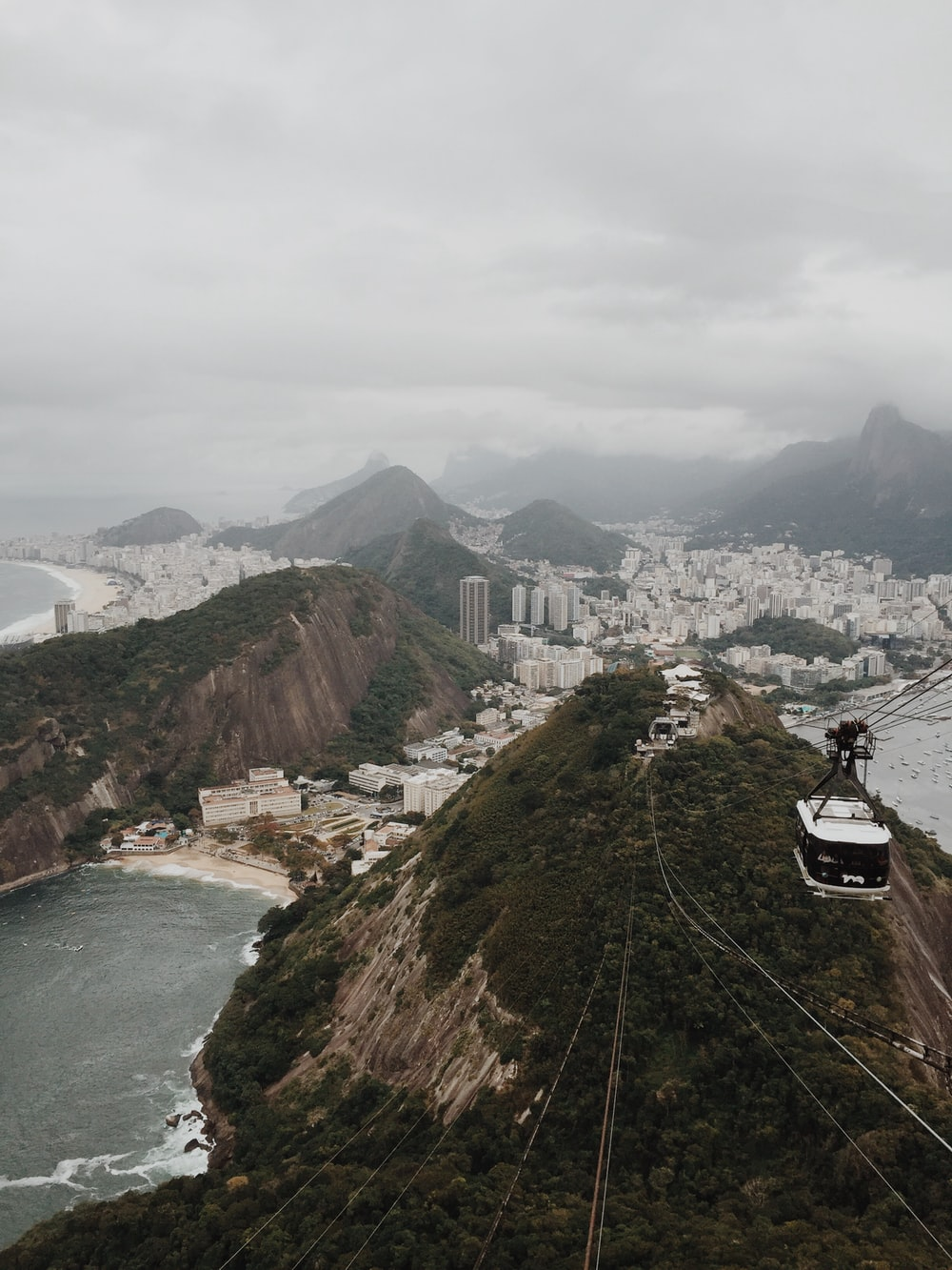 aerial photography of cable car above tree covered mountain