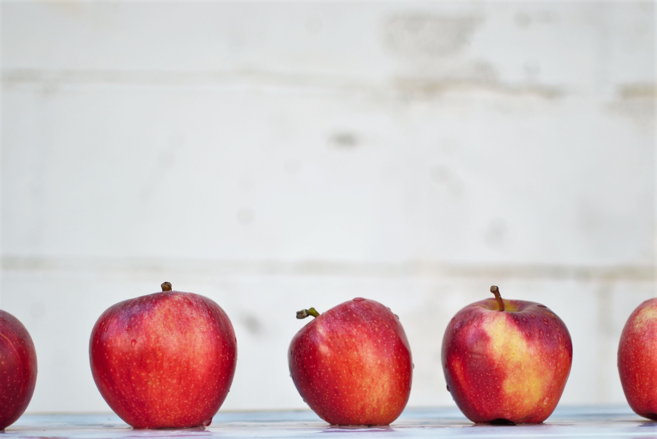 five red apples on white surface