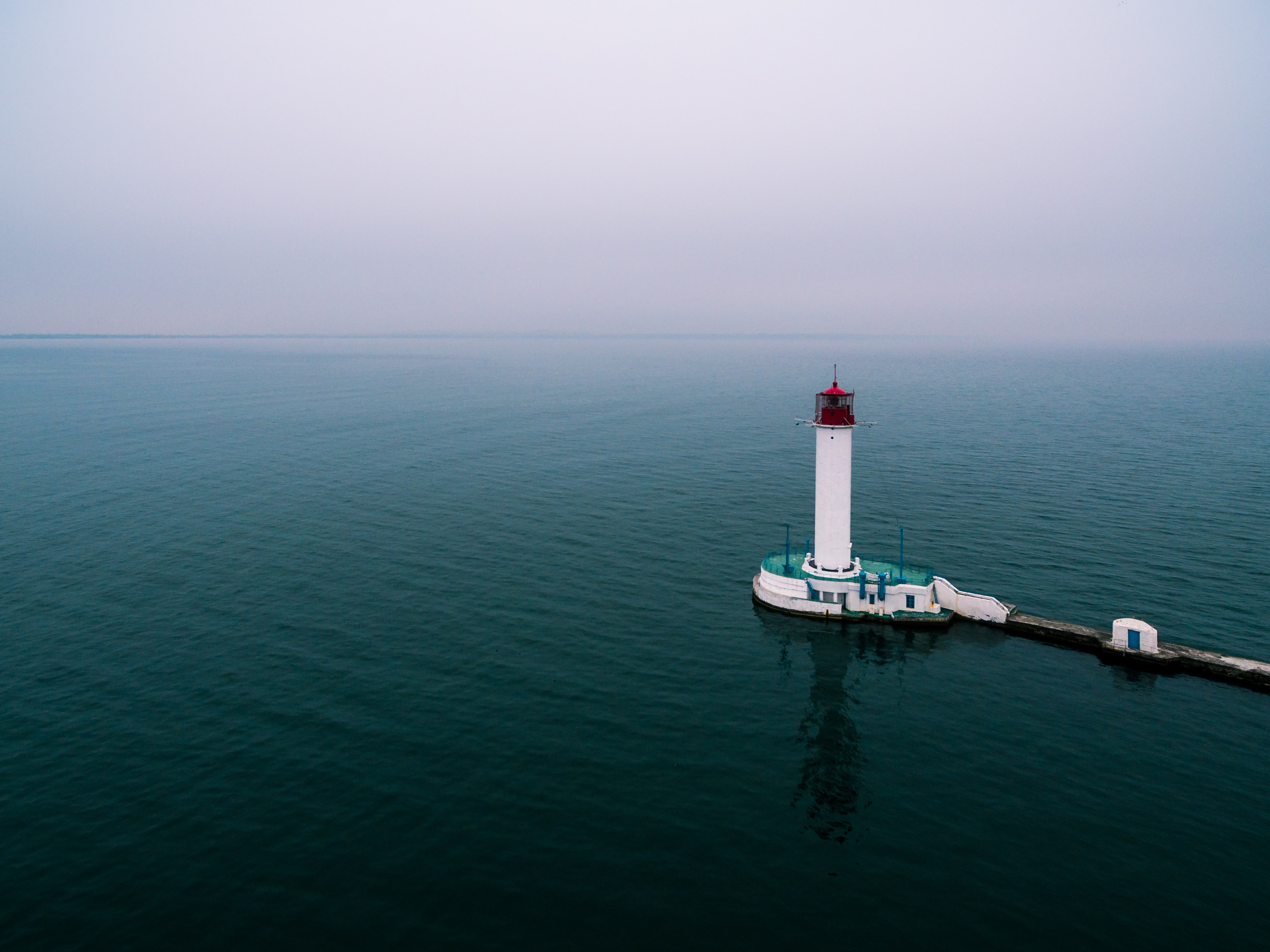 white and green lighthouse with body of water under white sky during daytime