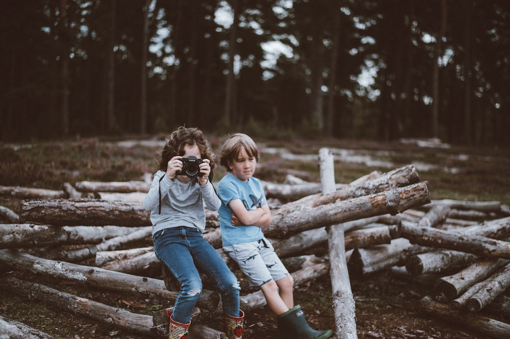 selective focus photography of boy and girl sitting on log