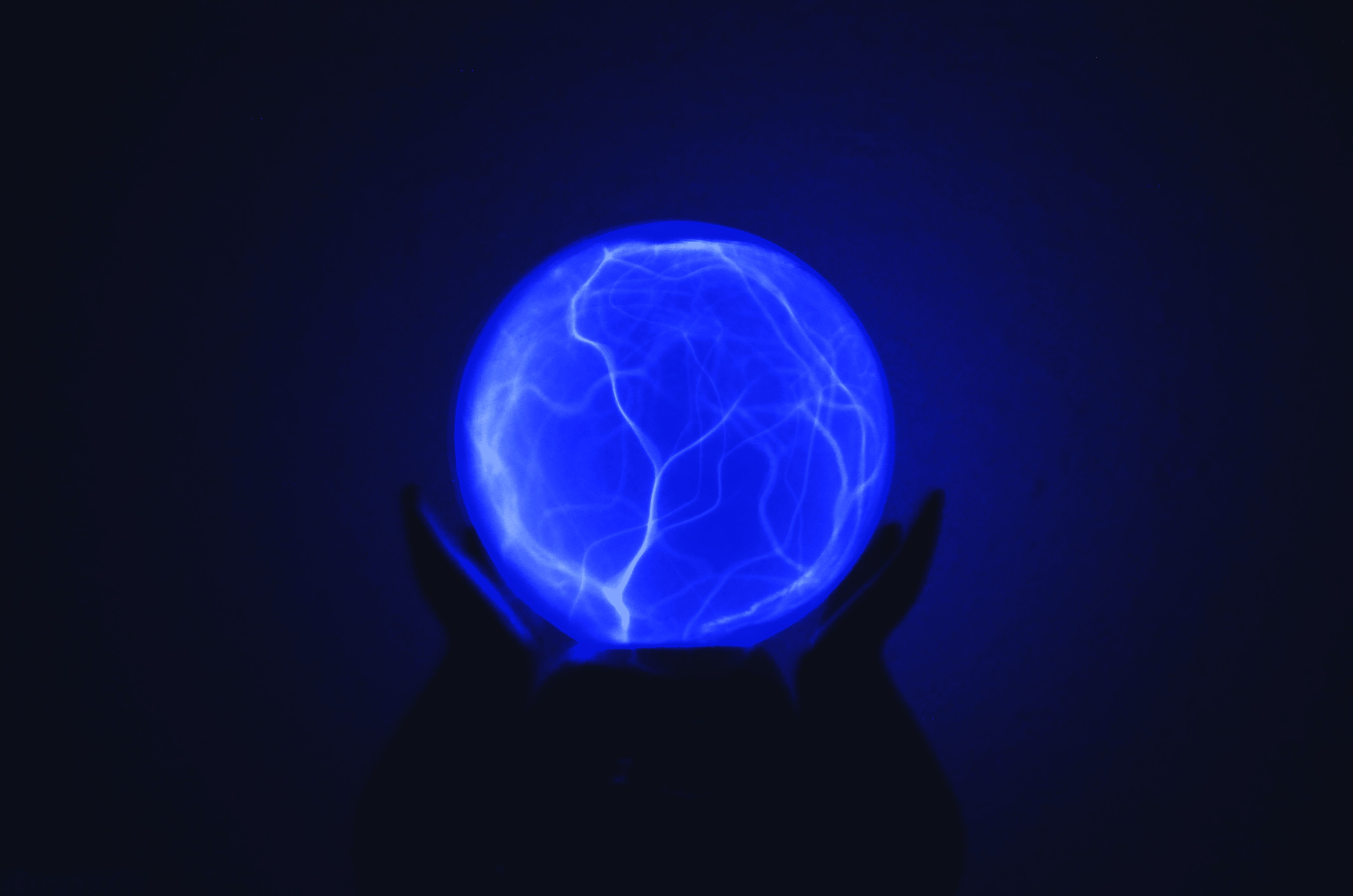 low light photo of person holding blue lighted ball
