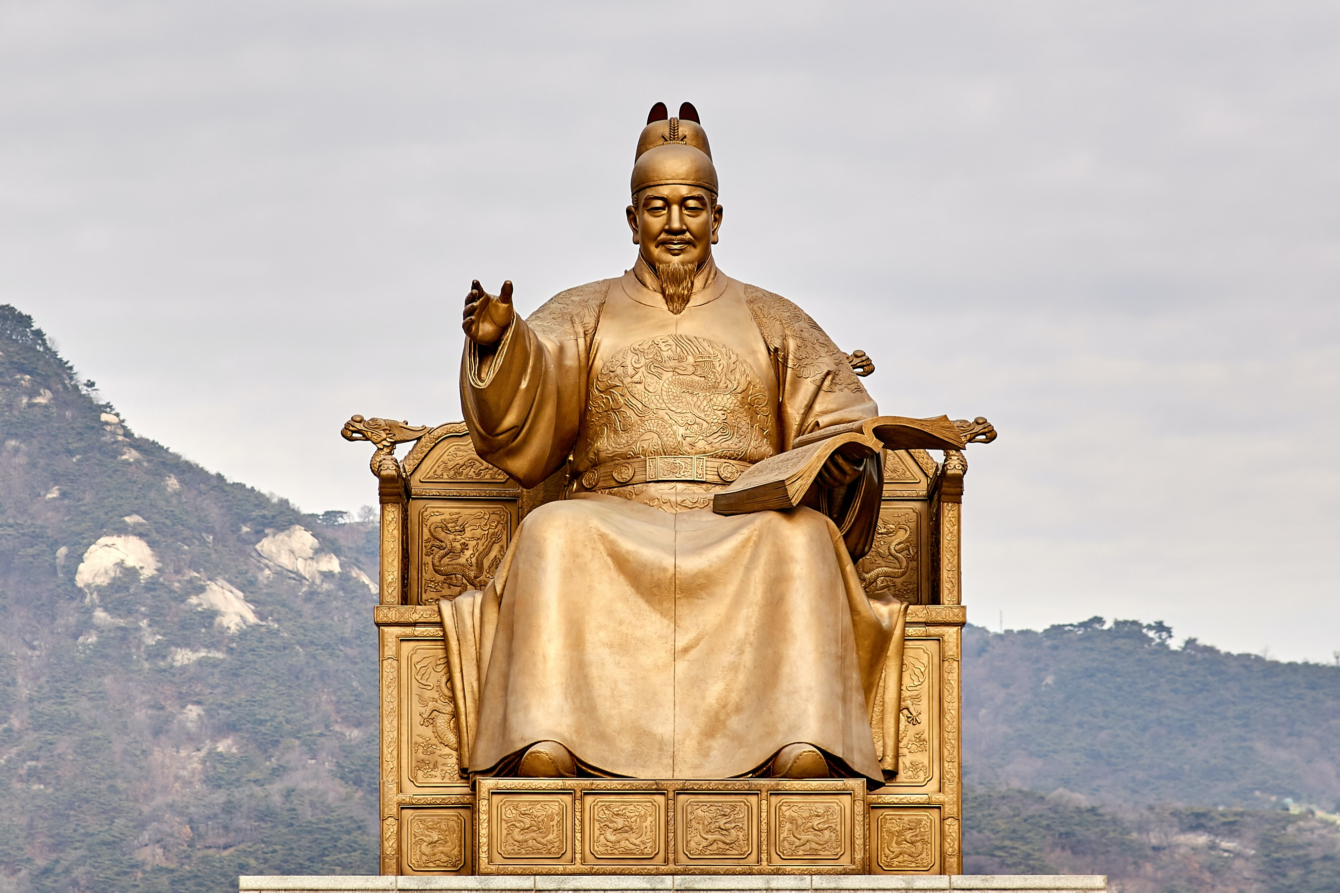 gold statue of man sitting on throne