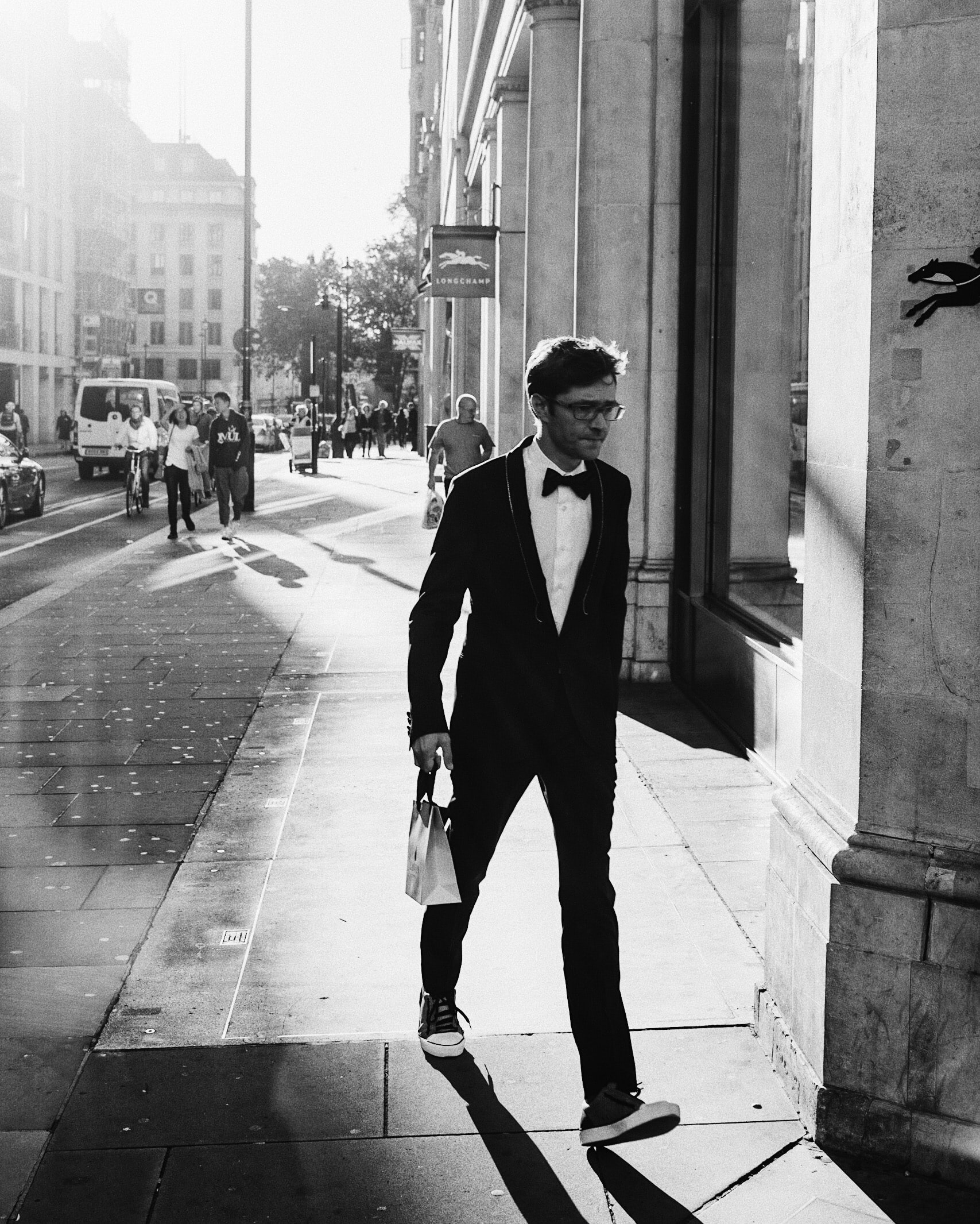 grayscale photo of man walking near concrete building