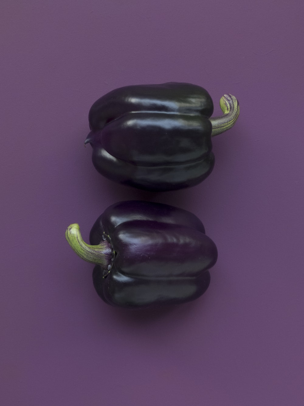 two purple bell peppers on purple surface