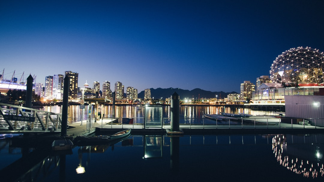 """I had just come home from a long day at work, and needed some time to just take in the beauty of this city. I struggled to find parking, worrying I would lose the last of the light for the evening. I wandered around Olympic Village (where this shot was taken), and ended up finding this… only to realize I forgot my tripod. I quickly set my camera down on the uneven ground, and made a makeshift """"stand"""" by levelling out the camera with the strap… And the shot captured the essence of Vancouver beautifully: a cityscape surrounded by beautiful mountains and the ocean grasping at its shores."""