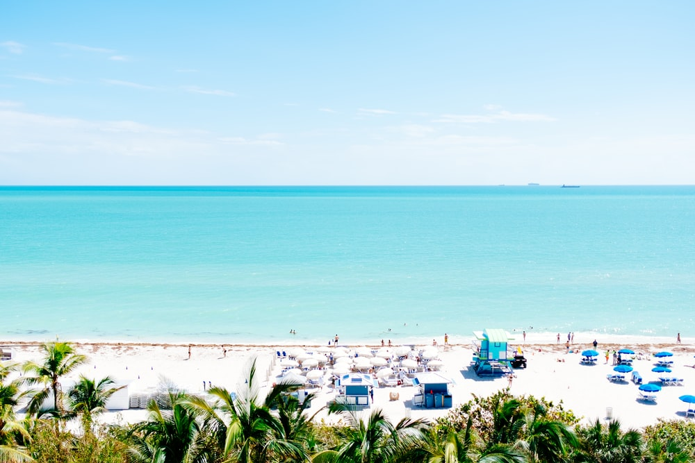 white sand beach with stalls under blue sky