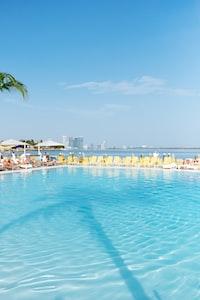 group of people sunbathing near pool