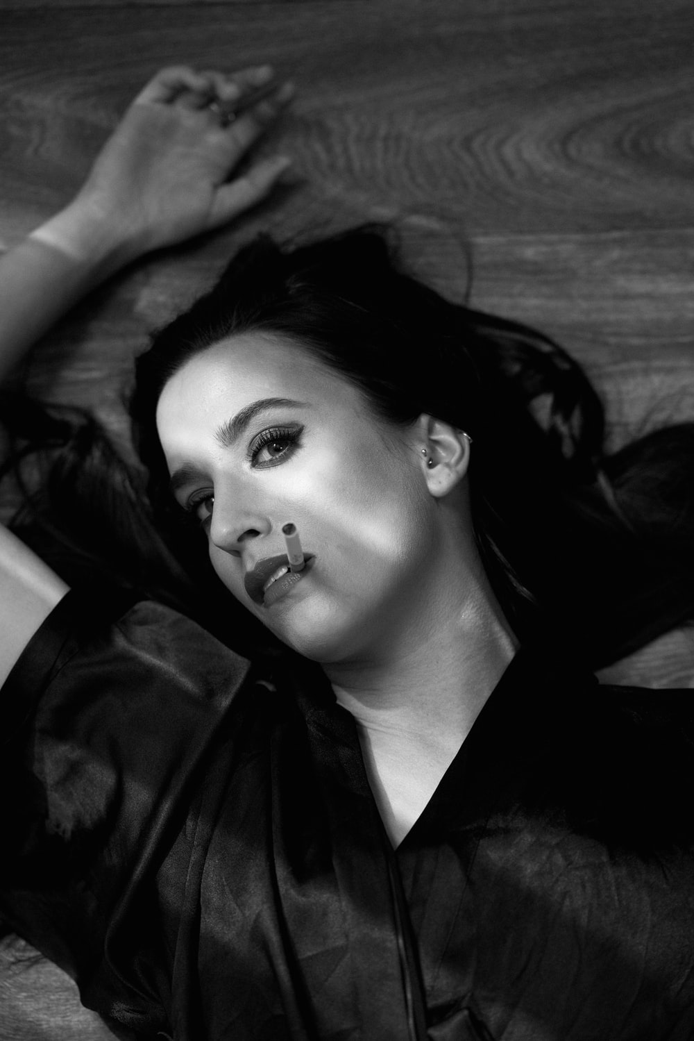 grayscale photography of woman lying on wooden surface