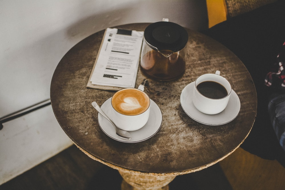 two coffee mugs with saucers on table
