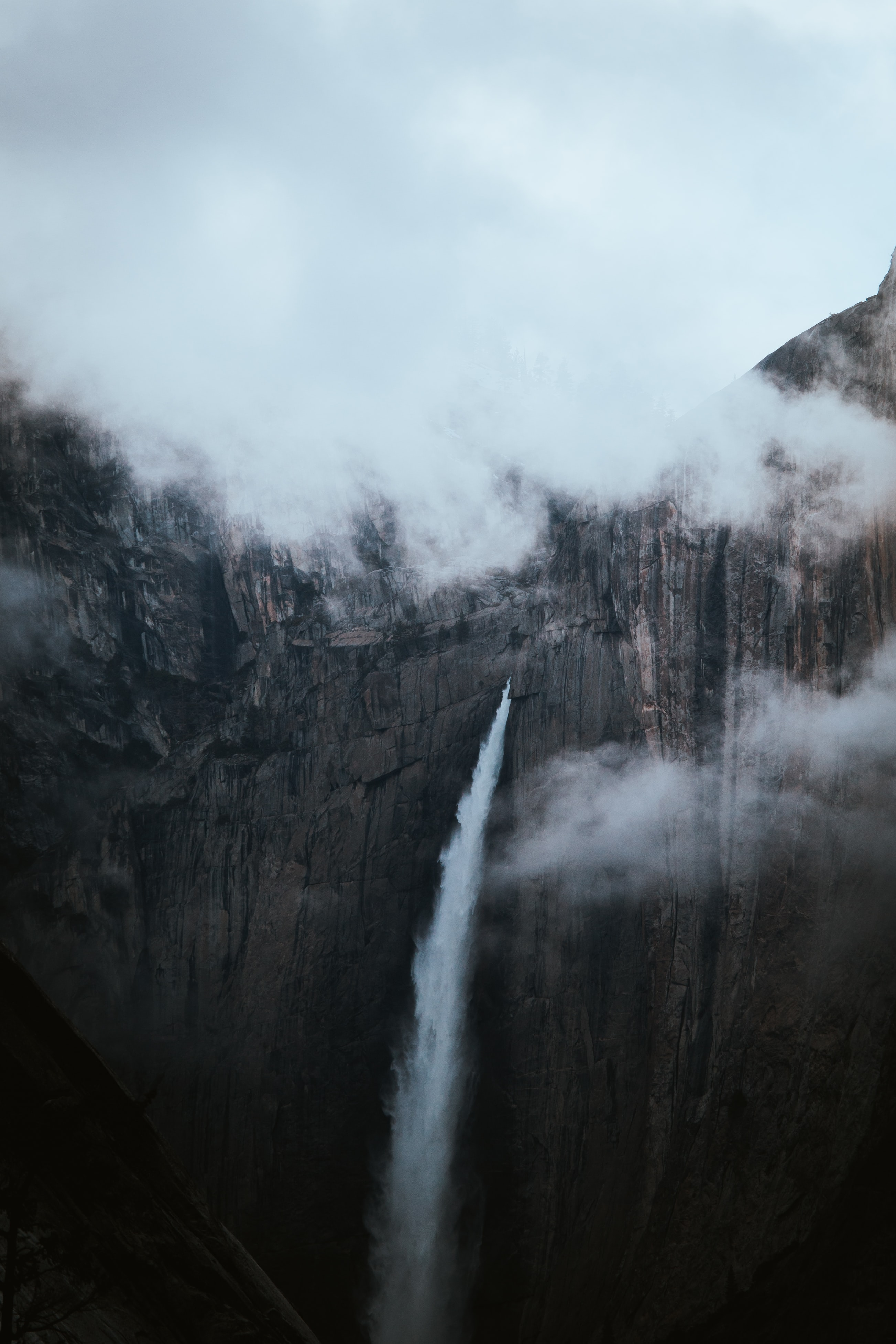 waterfall under white clouds at daytime