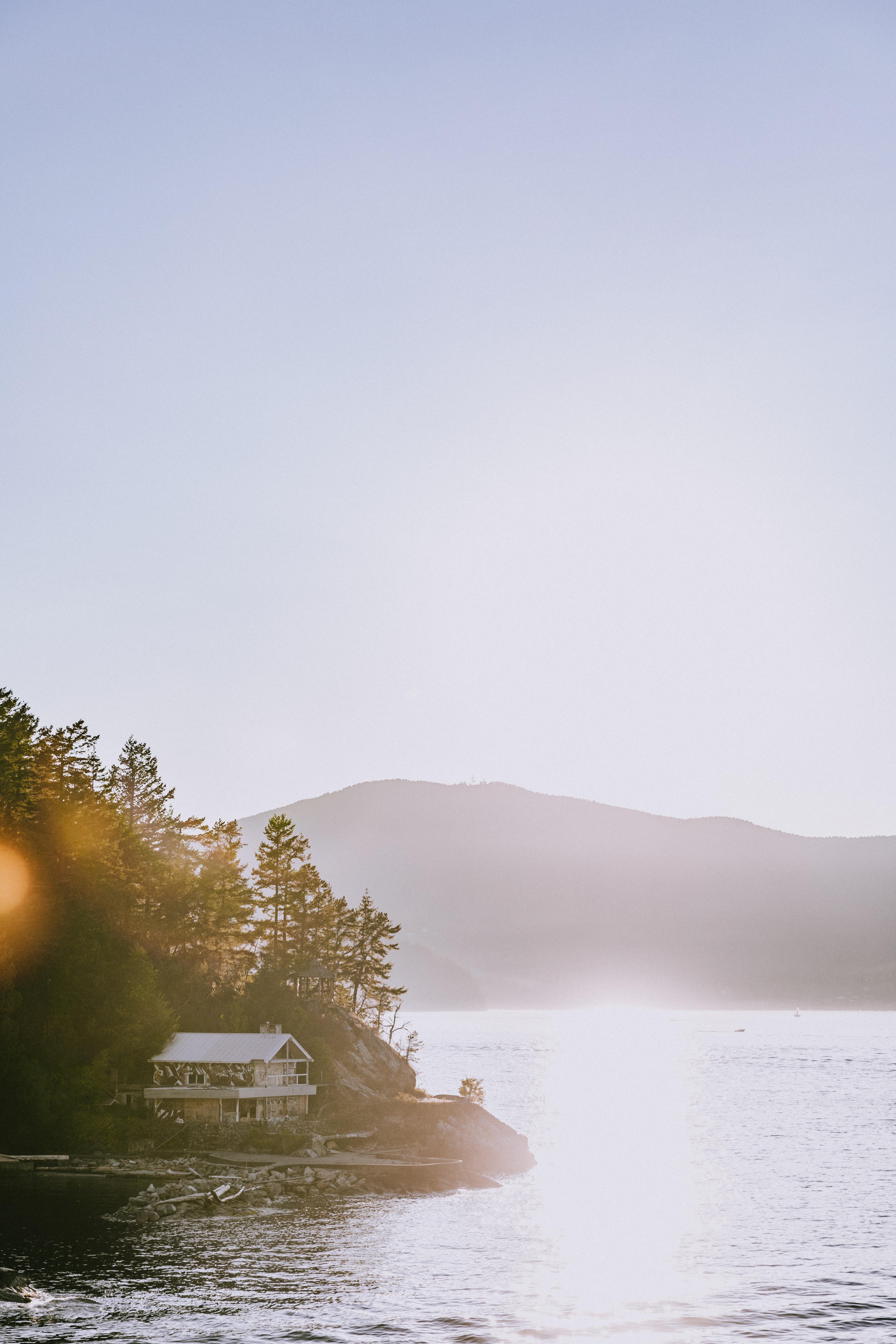 white cabin near body of water