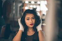 selective focus photography of woman holding her hair