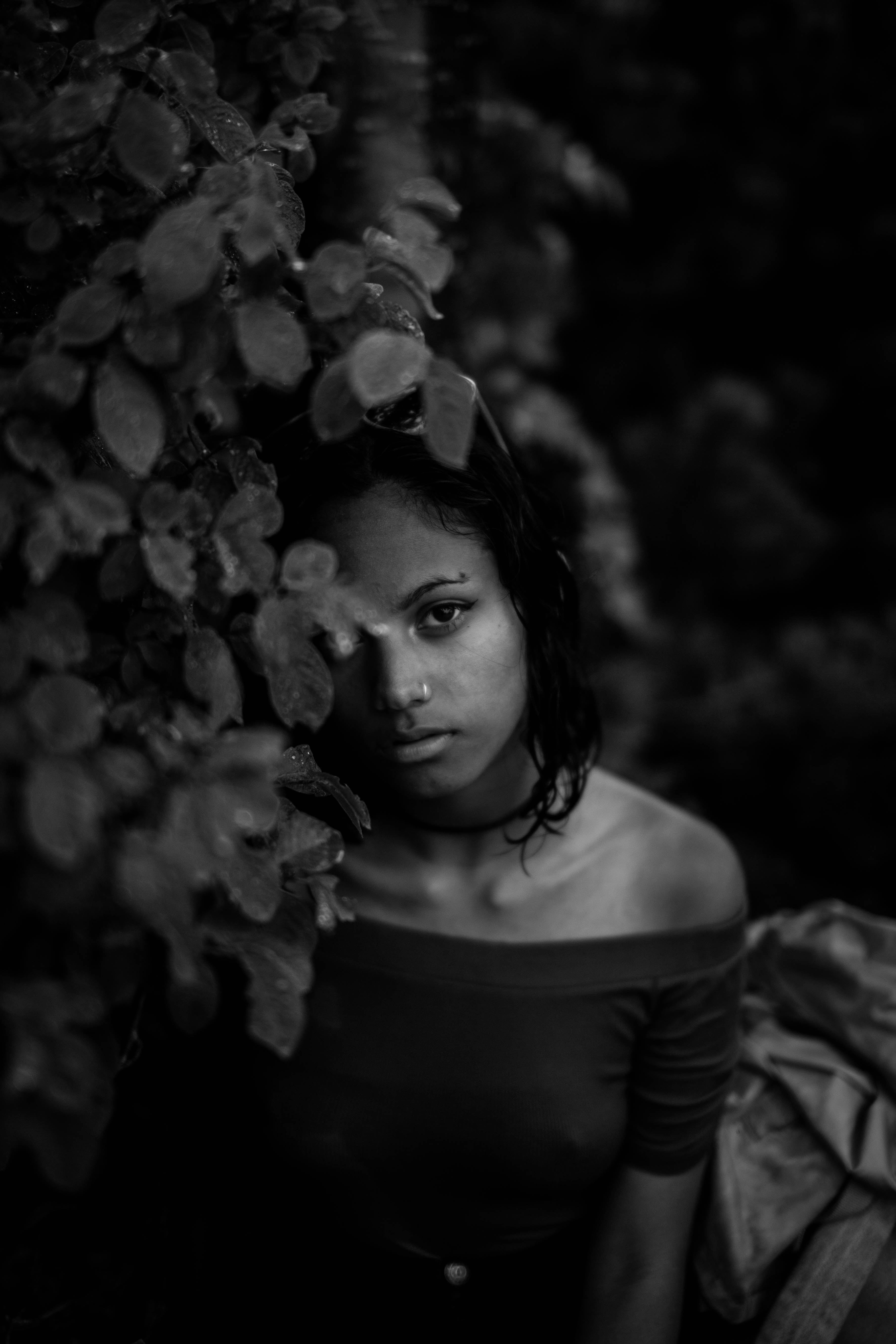 grayscale photography of woman beside vines
