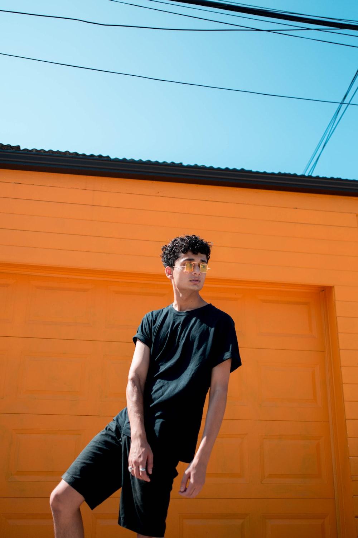 man in black crew-neck T-shirt and shorts standing in front of orange garage door