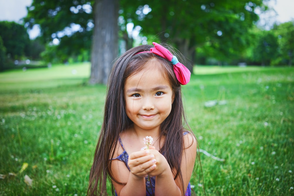 girl wearing black top while standing and holding flower on green grass