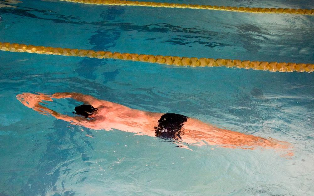 man swimming on pool