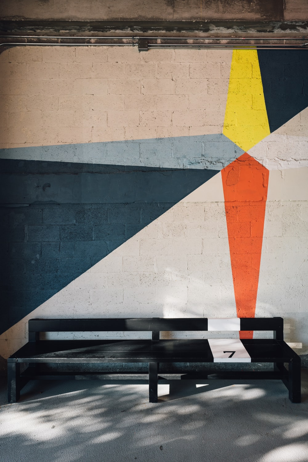 black wooden bench near white, blue, and orange painted wall