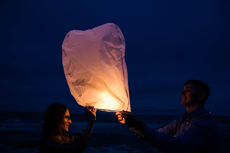 man and woman holding white sky lantern