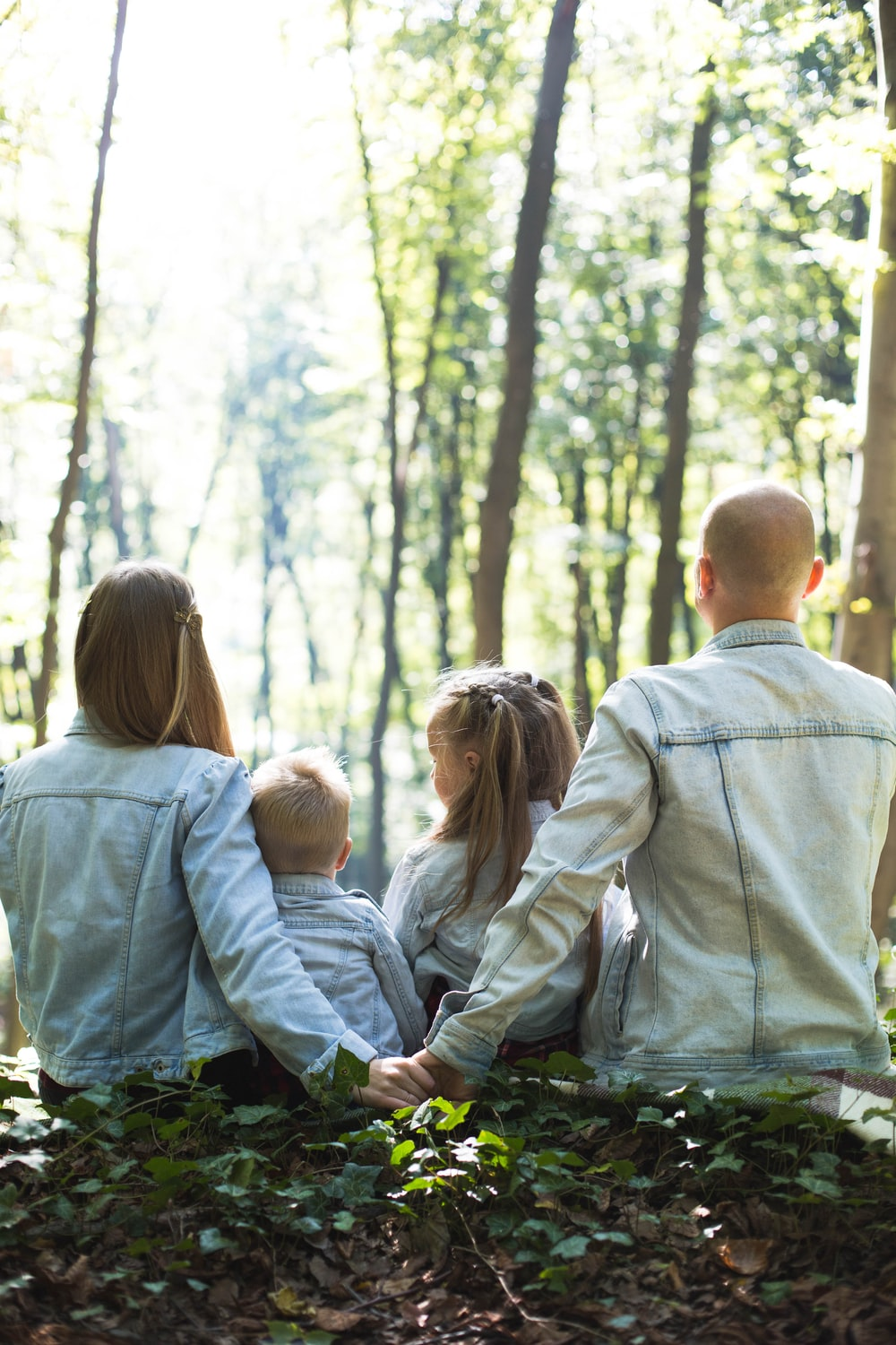 man and woman holding hands together with boy and girl looking at green trees during day