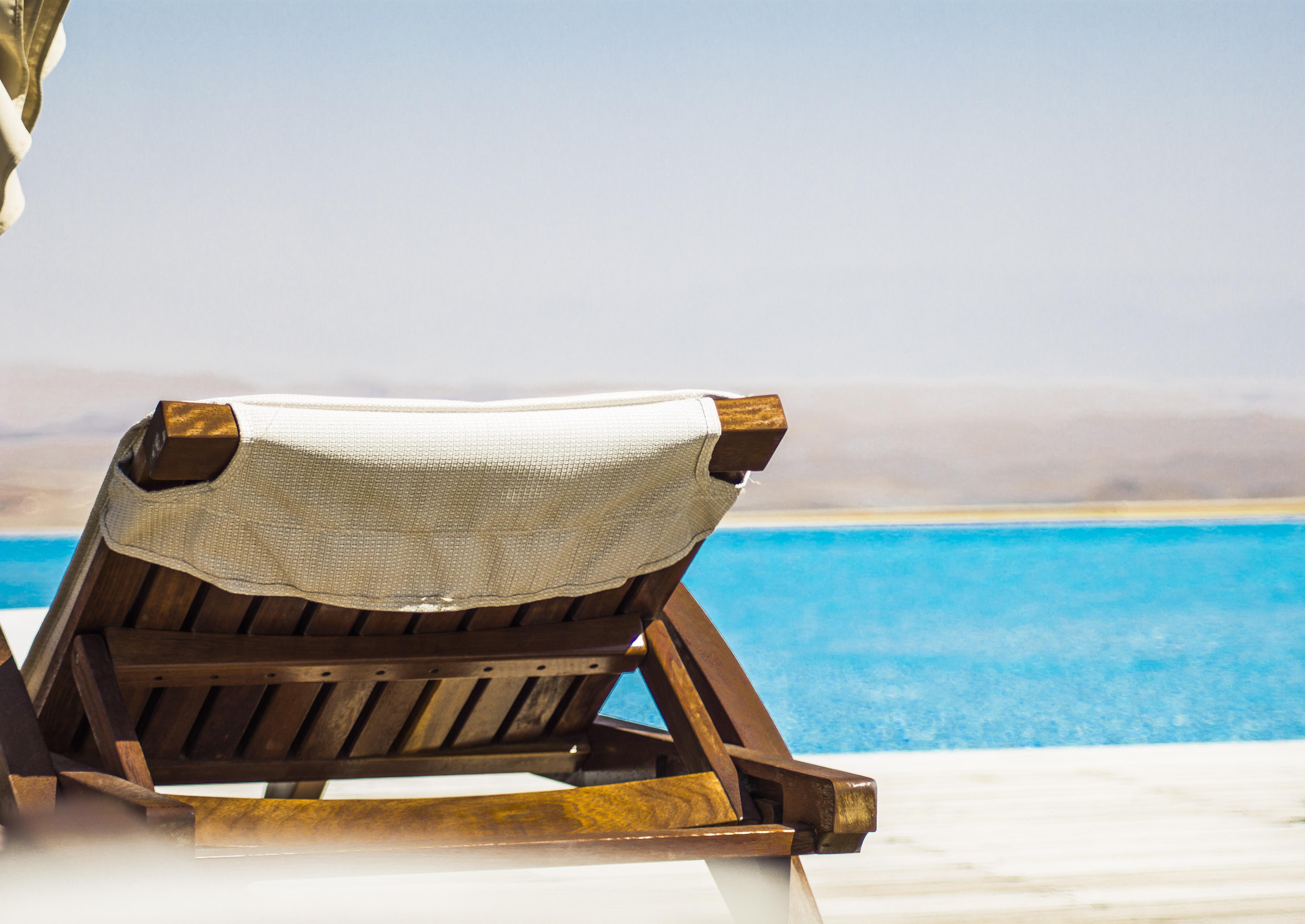 brown wooden lounger on seashore facing ocean