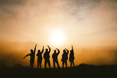 silhouette photo of six persons on top of mountain together teams background