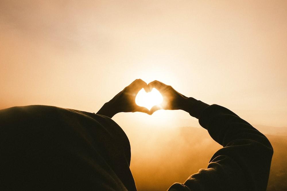 person doing heart shape hand with sun light passing thru