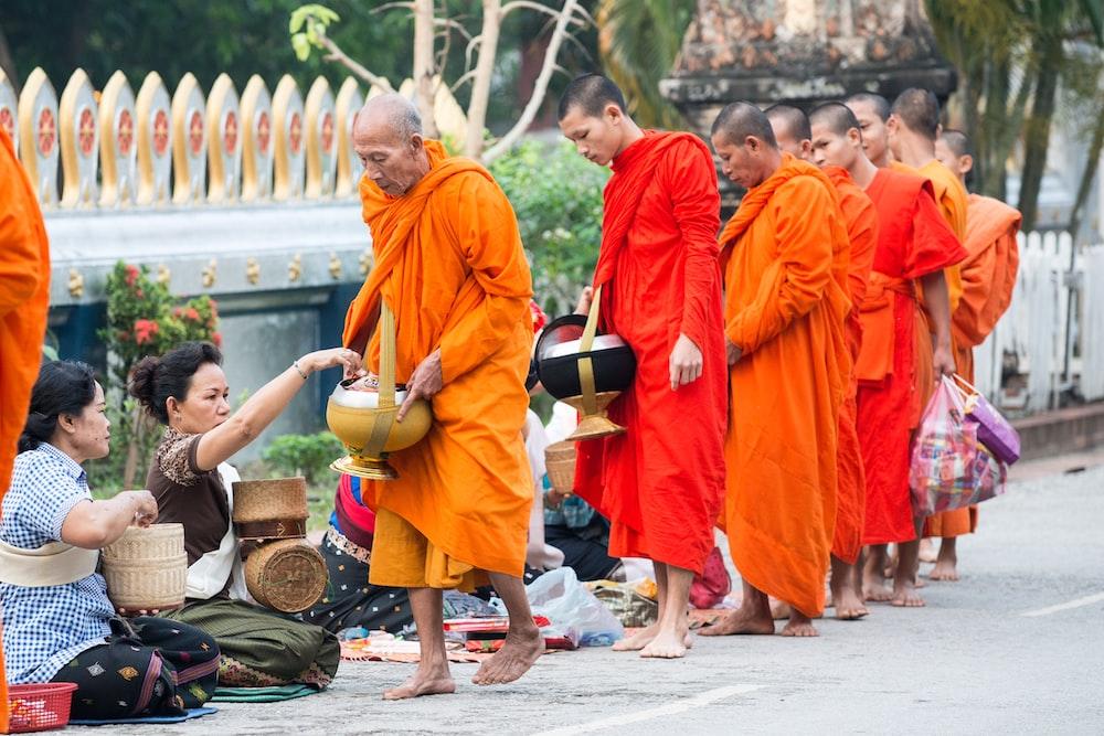 monks walking near people holding baskets on street