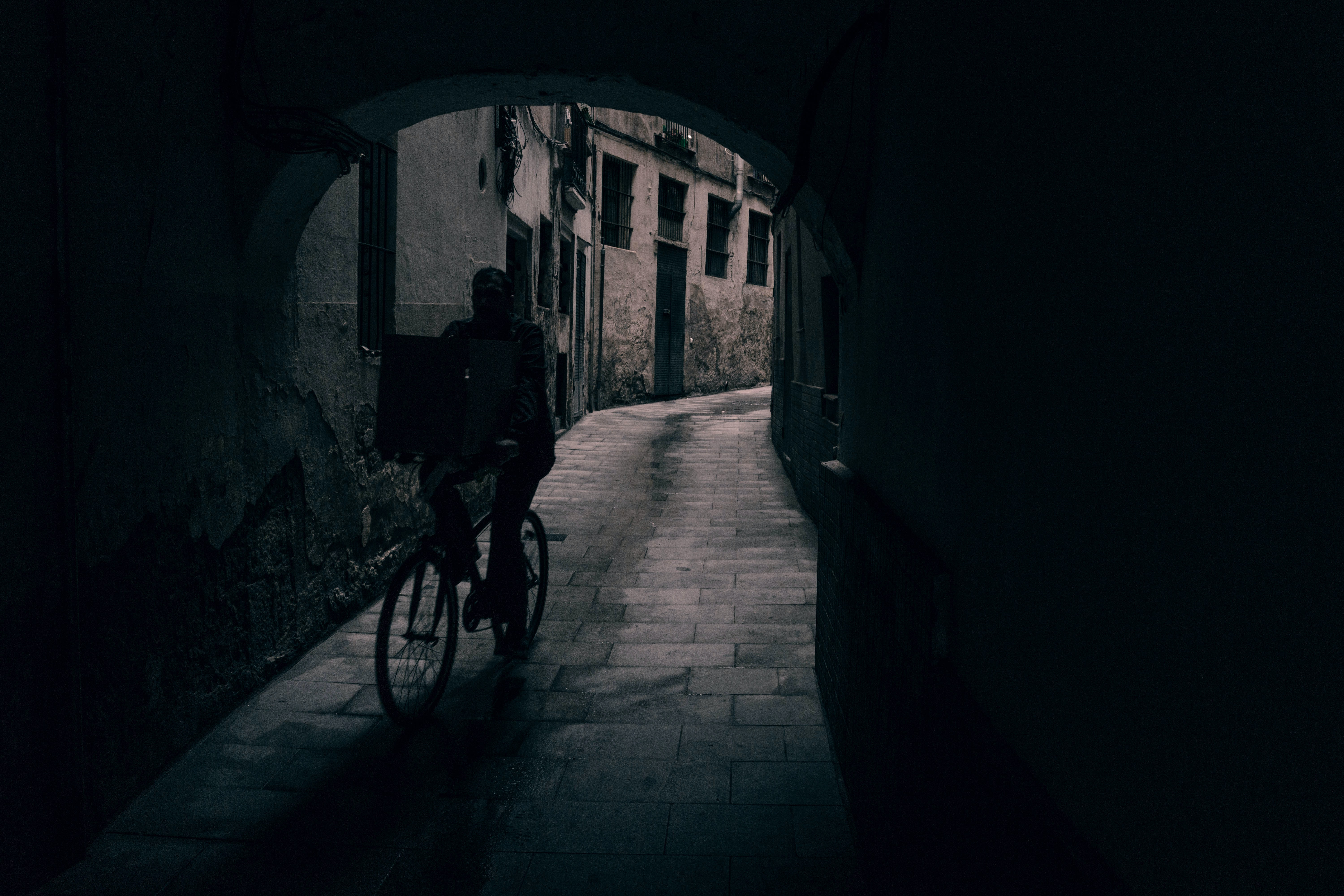 silhouette of person riding bicycle in tunnel