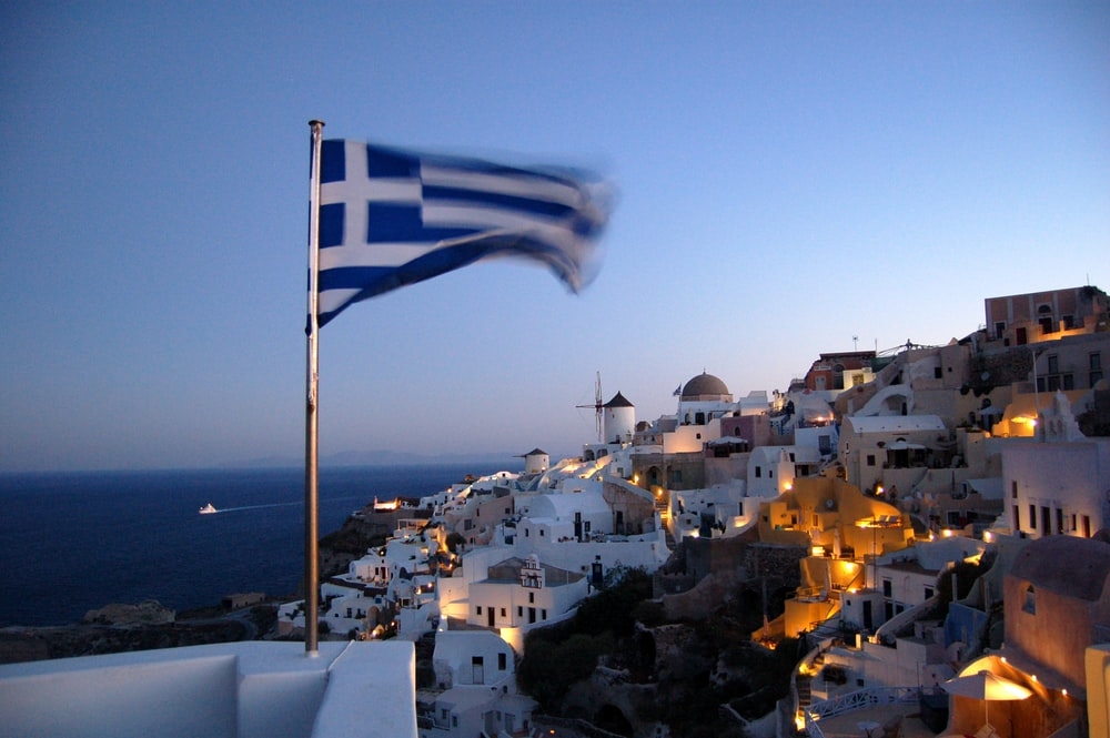 Flag of Greece waving at pole at Santorino, Greece