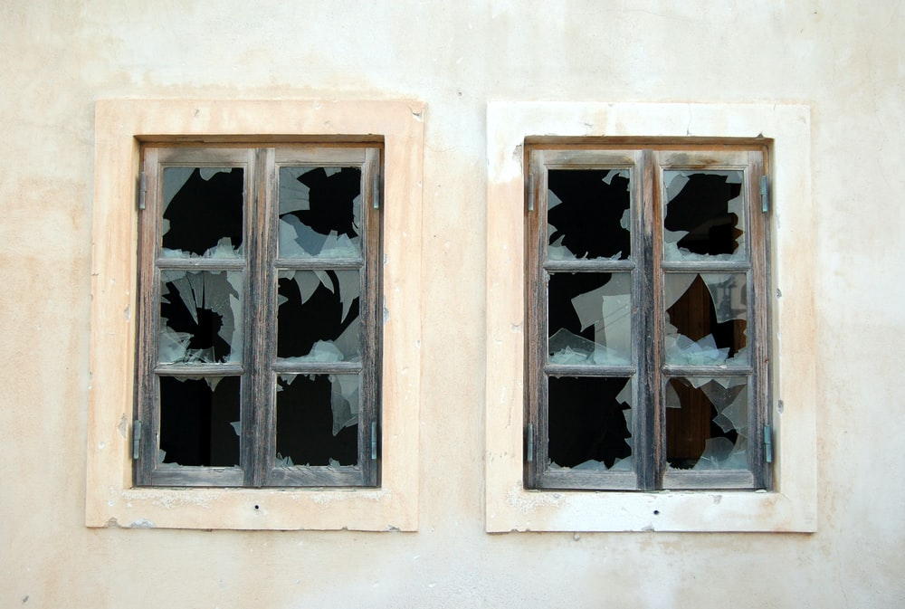two broken 6-pane windows on white painted wall