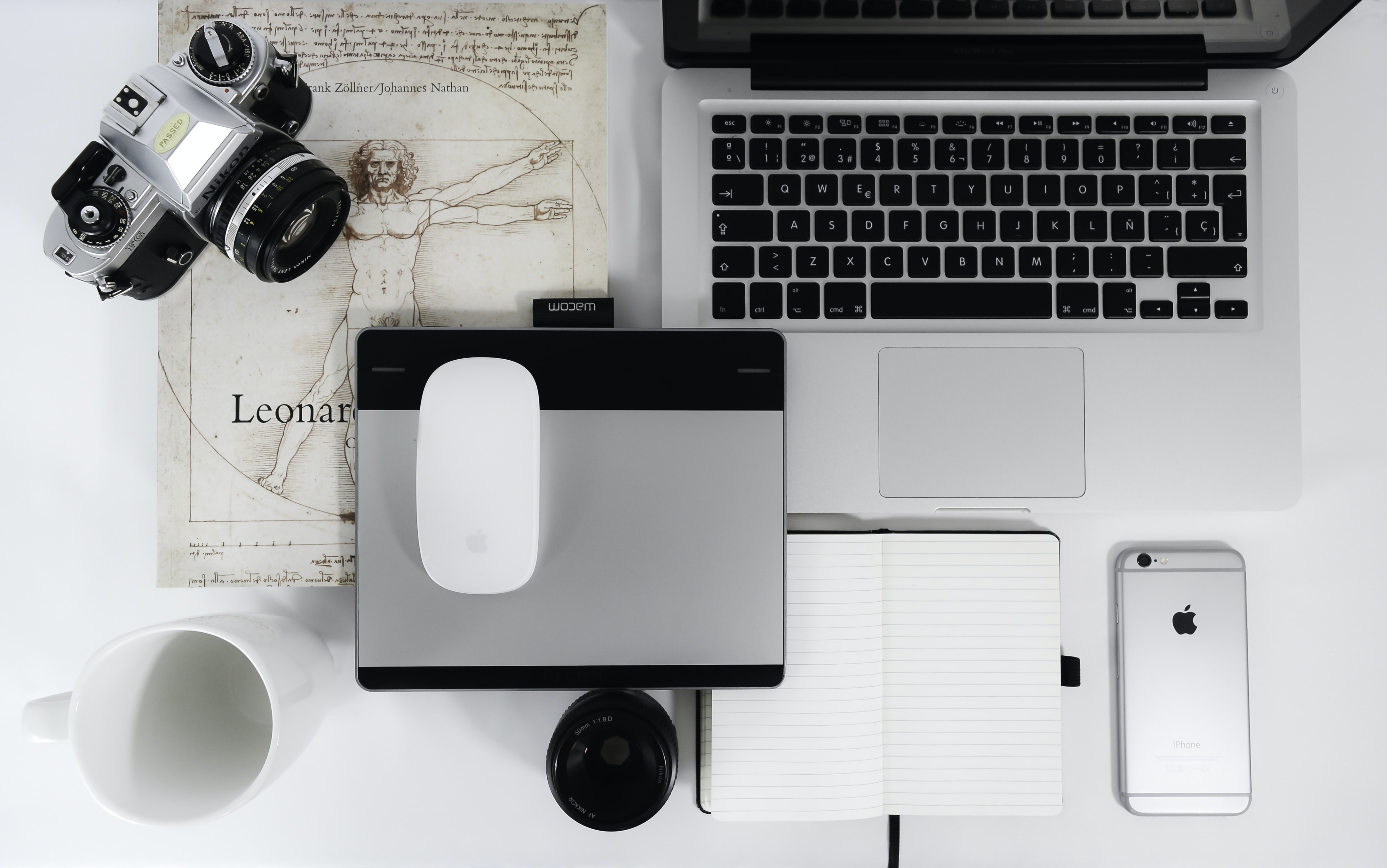 white Apple Magic Mouse, gray trackpad, gray SLR camera, space gray iPhone 6s, and MacBook Pro on table