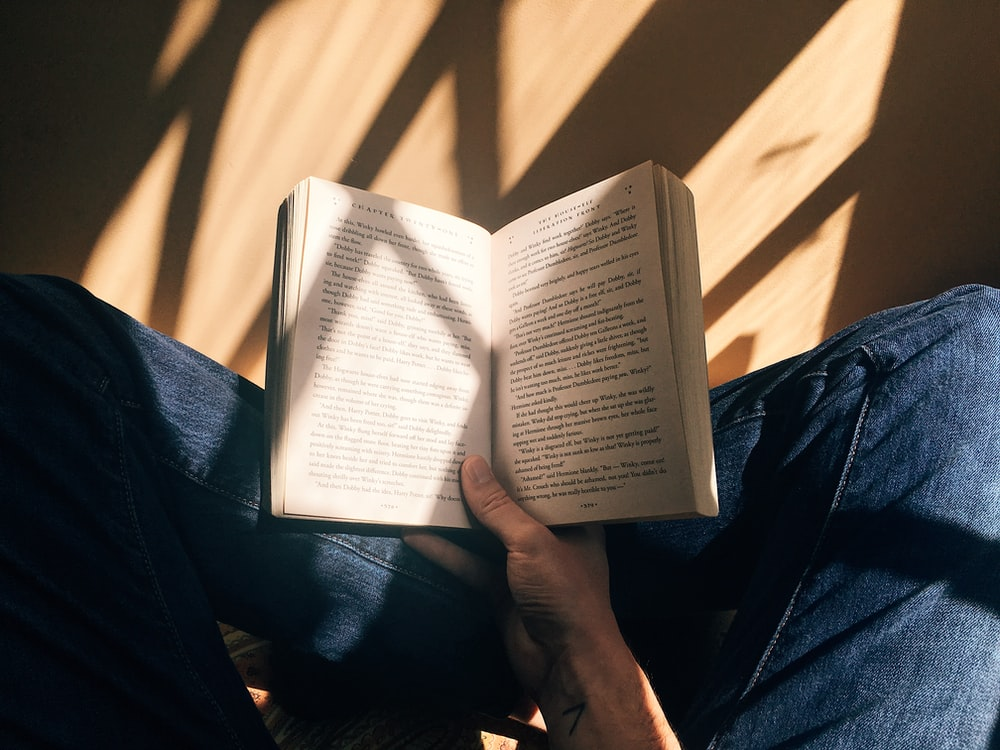 person holding book sitting on brown surface