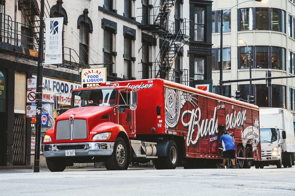 man near red Budweiser trailer truck parked near concrete building during daytime