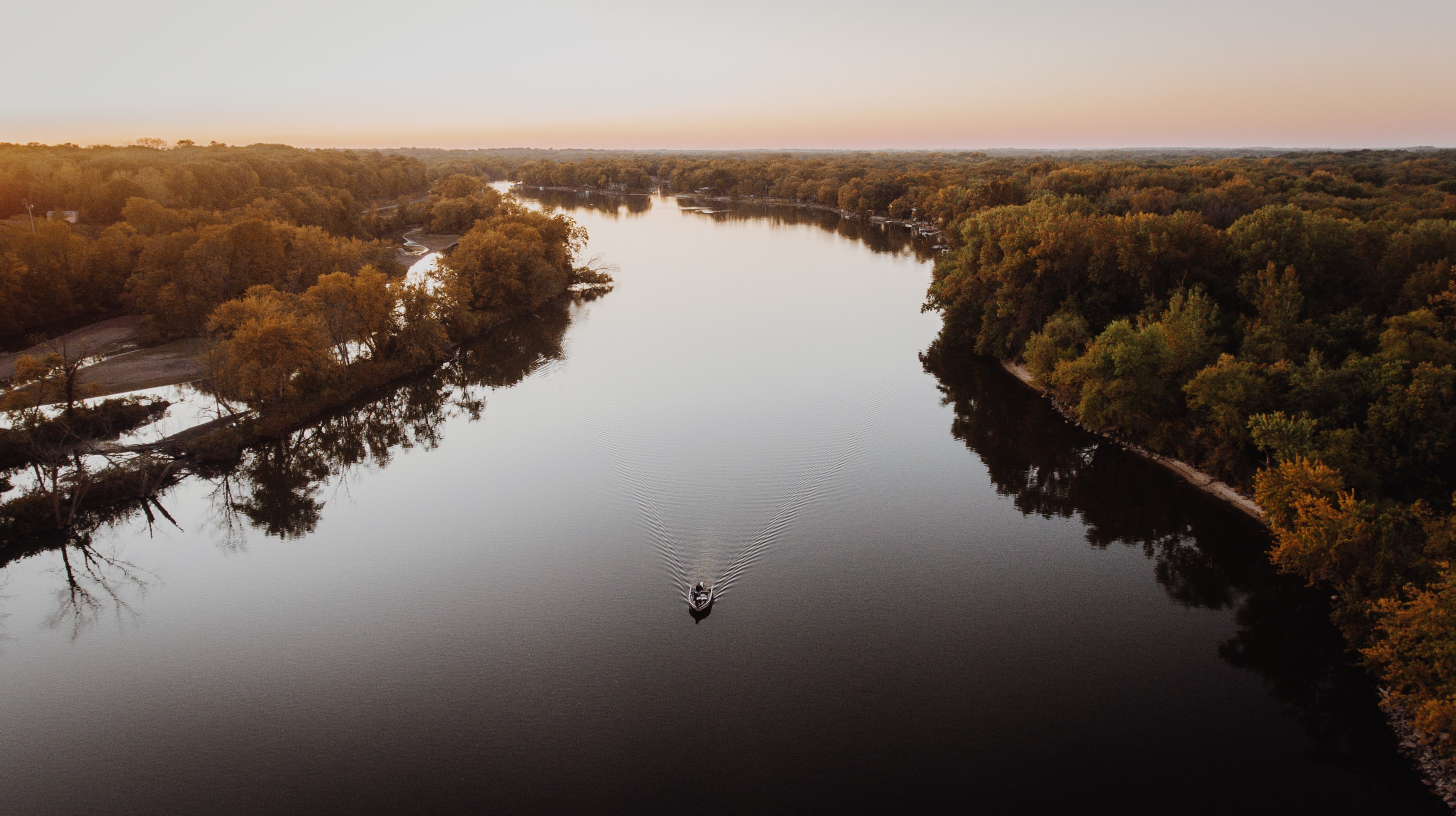 aerial photo of gray boat on flowing river near green trees