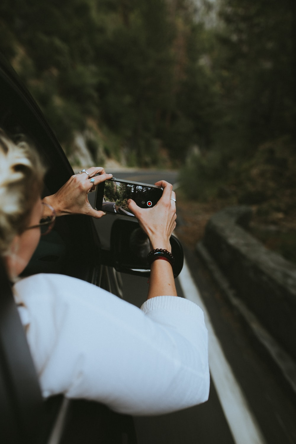 woman riding on the car holding smartphone taking a picture
