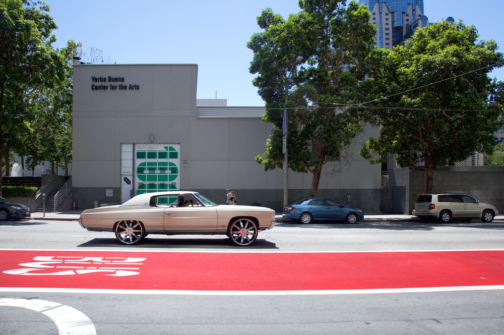 silver coupe in front of building