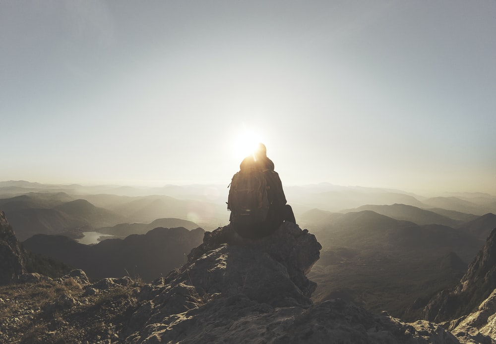 silhouette of person sitting on rock facing mountain range