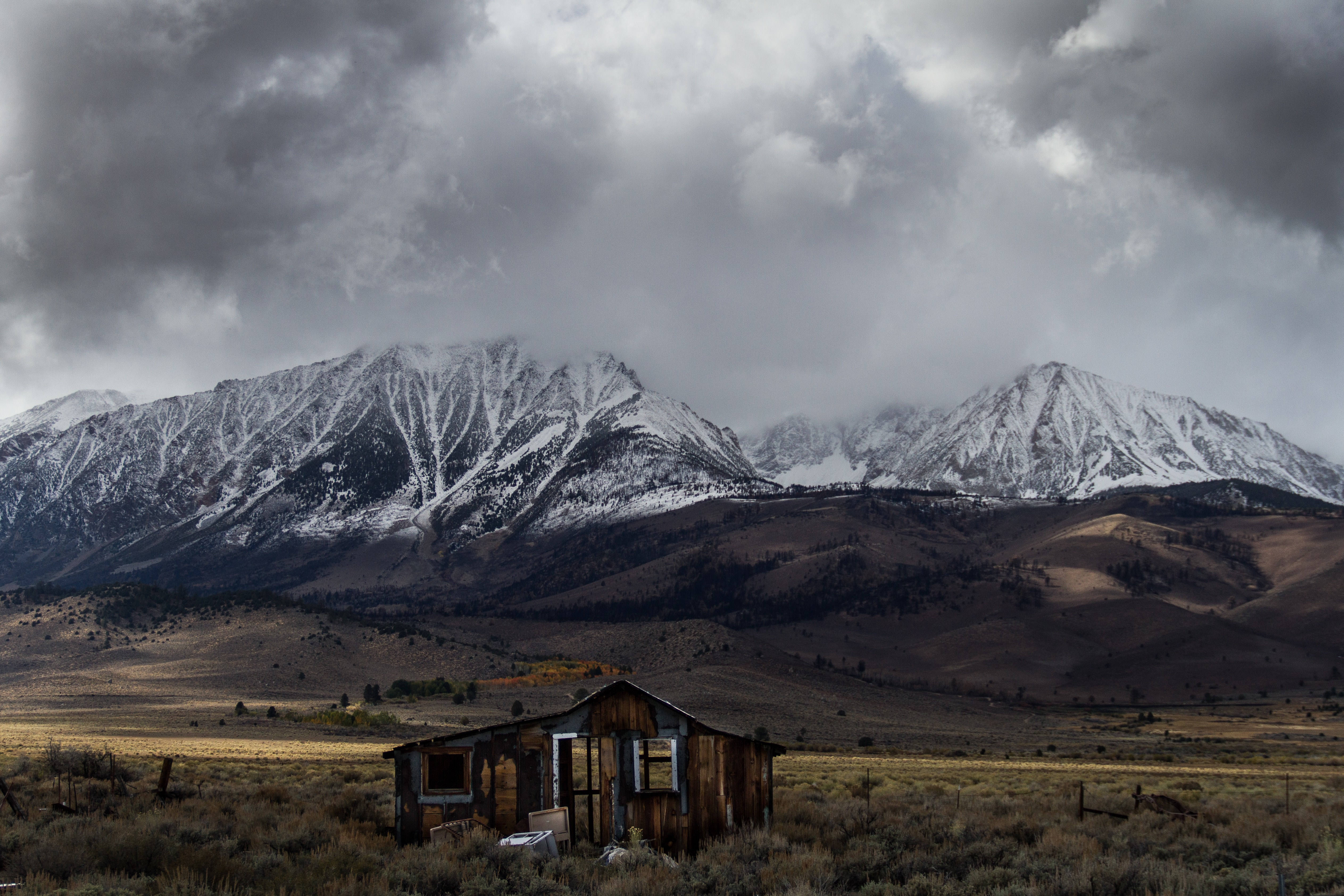 abandoned brown wooden cabin at middle of valley with view of snow-covered mountain range under gray cloud formation during daytime