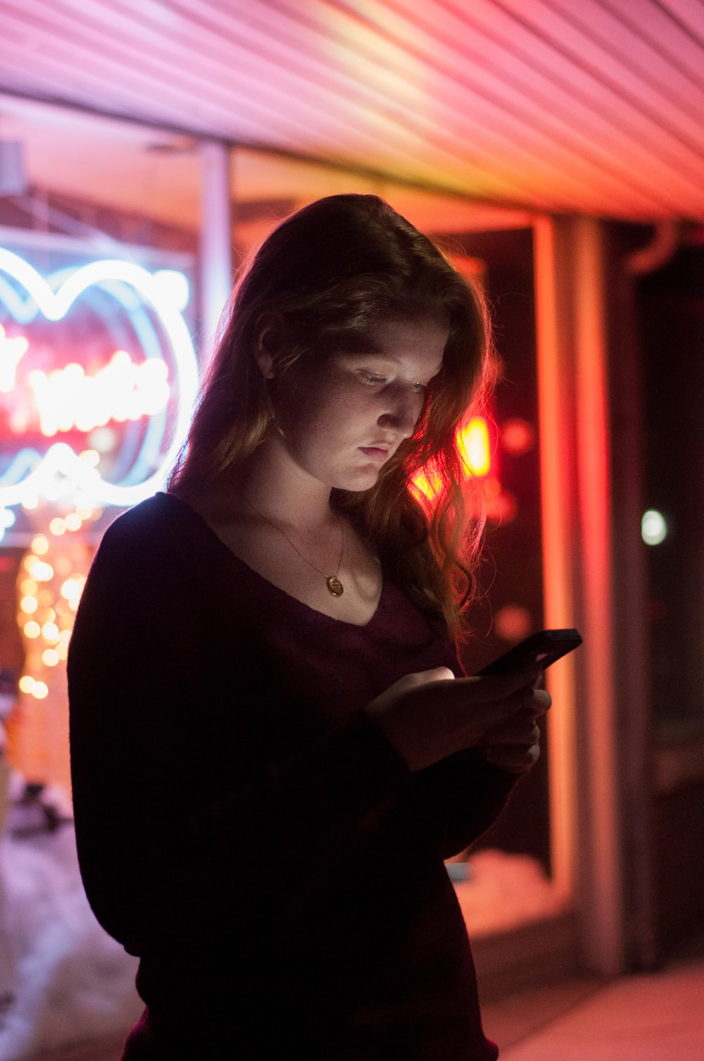 woman using smartphone in front of red and blue lighted glass store