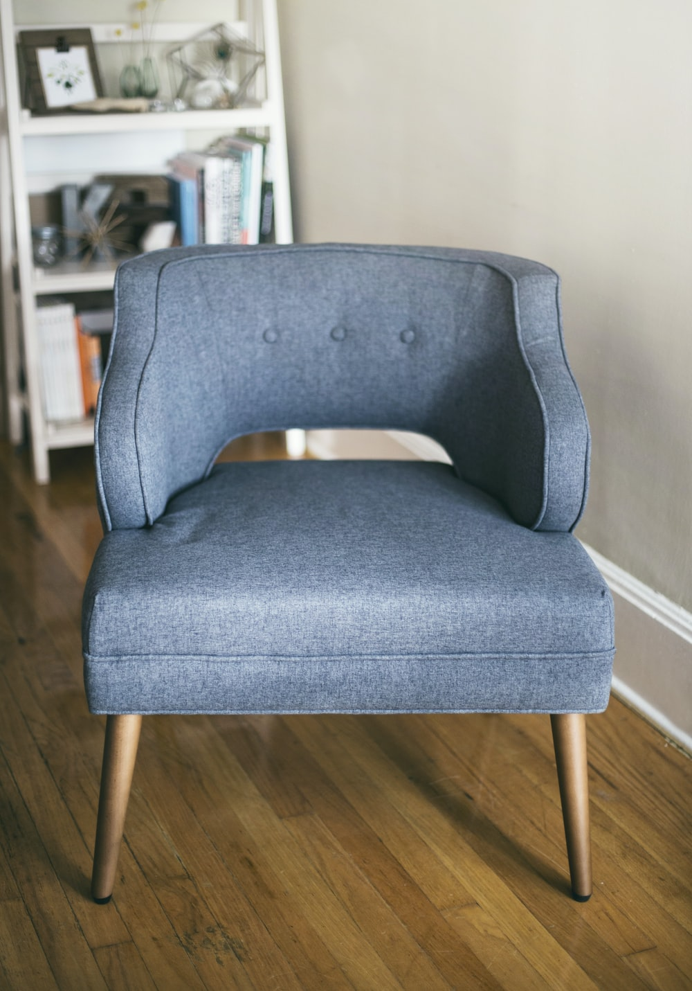 person taking photo of grey padded chair inside room